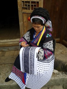 My village hostess wearing the Buyi traditional costume and displaying batik-drawing during an annual Buyi festival. Photo courtesy of Yu Luo.